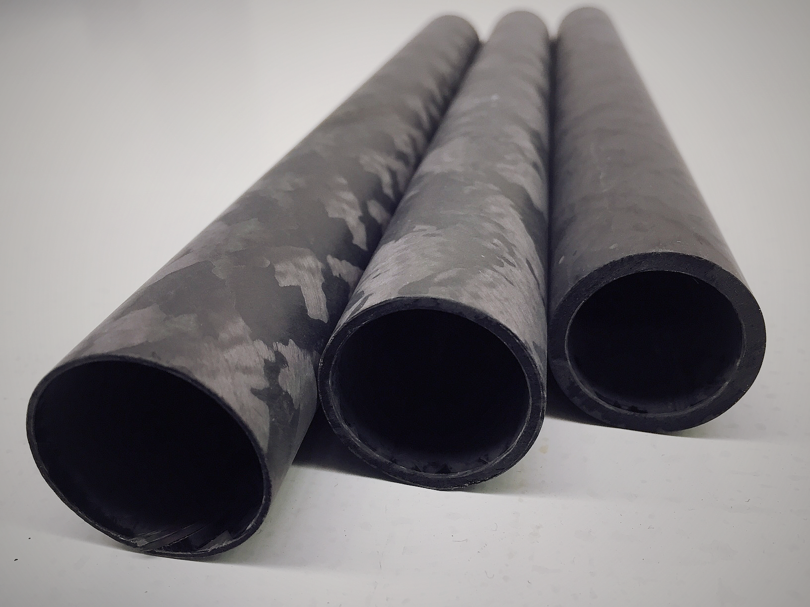 Close Up of three Carbon Fibre Tubes in a Row